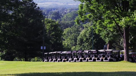 Golf carts lined up on a golf course. Establishing shot at a golf range in the summer time. Peaceful view of green lawn and trees at a golf club house.