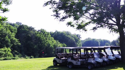 Golf carts lines up along a fairway at a local golf course. Establishing shot f an empty golf range during a clear sunny summer day. Beautiful golf course.
