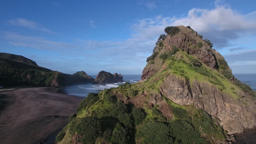 Aerial view of Lion Rock and large surf waves at Piha Beach, Auckland, New Zealand