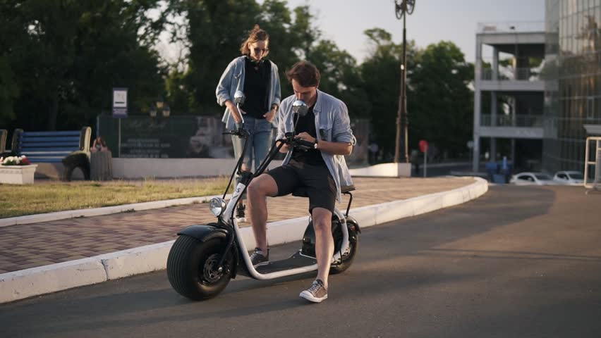 Young couple spending time together. Attractive girl closes boyfriend's eyes from the back. He's sitting on a bike. Summer day. Happy young couple | Shutterstock HD Video #1012993865