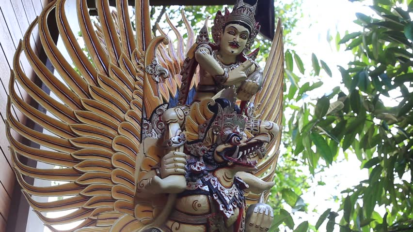 Balinese ancient colorful bird god Garuda with wings, close up. Religious traditional statue from wood. Wooden old curved figure of Hindu god in Island Bali, Ubud, Indonesia