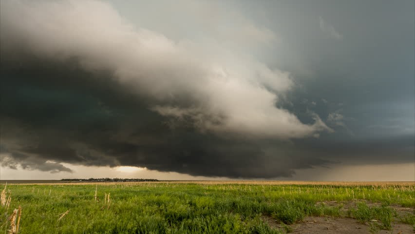 A large tornadic mesocyclone supercell inflow with a green glow of hail sucks in energy as it begins to transform into a tornado. | Shutterstock HD Video #1013016905