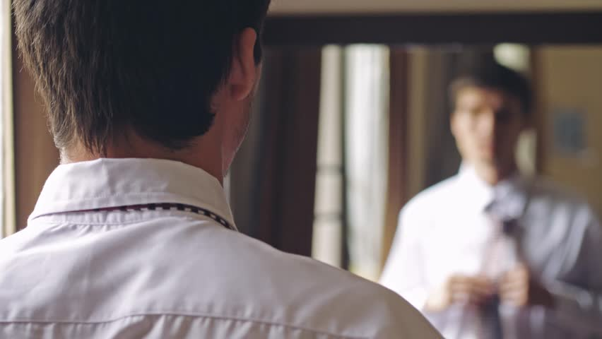 Yomg handsome man in white shirt stands by the mirror tying a tie. To chenges focus from man to the mirror. 3840x2160