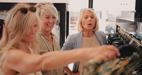 Happy elegant mature women having fun searching and shopping for clothes in city store