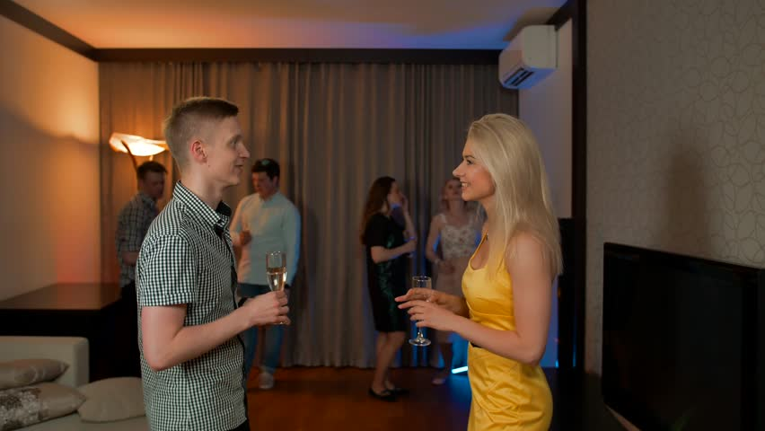 Sexy young couple meet flirting at glamorous party drinking champagne cocktail in love having fun together feeling attraction.