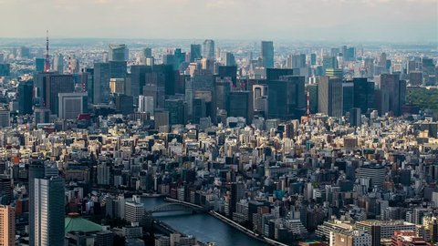 Tokyo Aerial View. Time-lapse panorama from high point. Clouds over the city cast shadows.