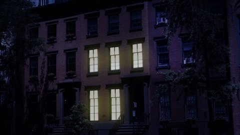 A nighttime exterior establishing shot of a typical Brooklyn brownstone residential row house. Window lights turn on and off. Simulated day-for-night treatment. Day/Night matching available.