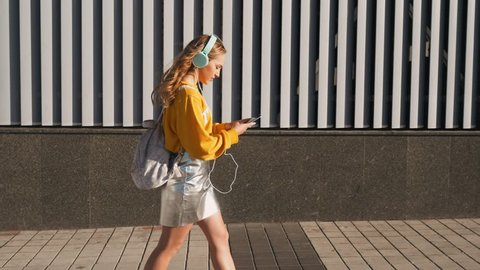 Portrait of young cute attractive young girl in urban background listening to music with headphones. Woman wearing yellow blouse and silver skirt.