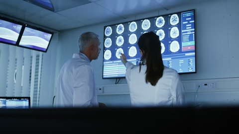 Two Medical Scientists / Neurologists, Talking and Pointing at Wall TV Showing CT / MRI Brain Scans in Modern Laboratory.  Shot on RED EPIC-W 8K Helium Cinema Camera.