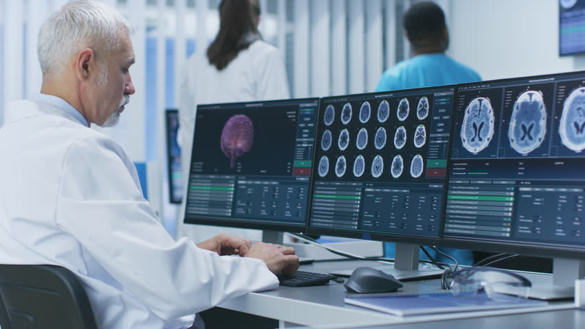 Experienced Senior Scientist Working with CT/ MRI Brain Scan Images on a Personal Computer in Laboratory. Neurologists / Neuroscientists in Medical Research Center. Shot on RED EPIC-W 8K Helium Camera