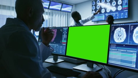 Medical Scientist Working with Mock-up Green Screen and CT Brain Scan Images on a Personal Computer in Laboratory. Neuroglogists work in Neuroscience Research Center. Shot on RED EPIC-W 8K Camera.