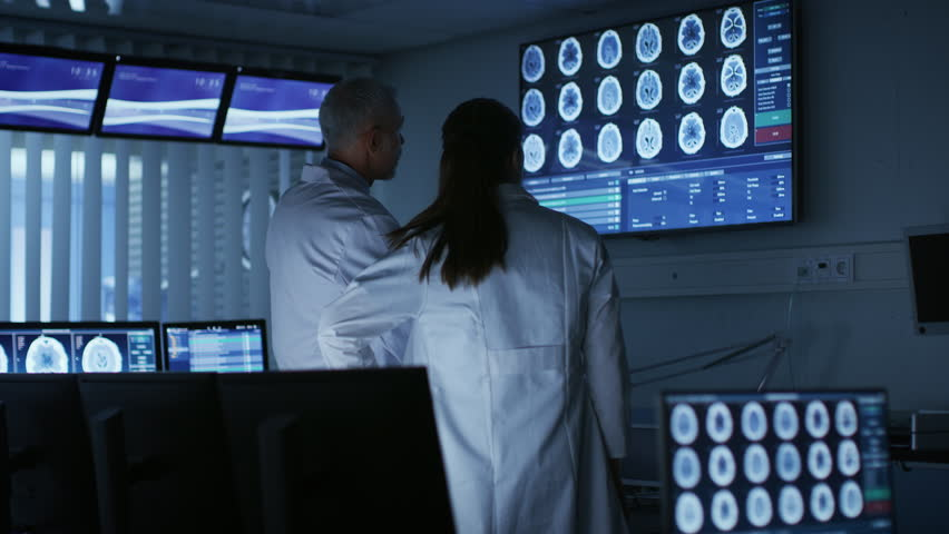 Two Medical Scientists / Neurologists, Talking and Working on a Personal Computer in Modern Laboratory. Research Scientists Making New Discoveries. Shot on RED EPIC-W 8K Helium Cinema Camera.