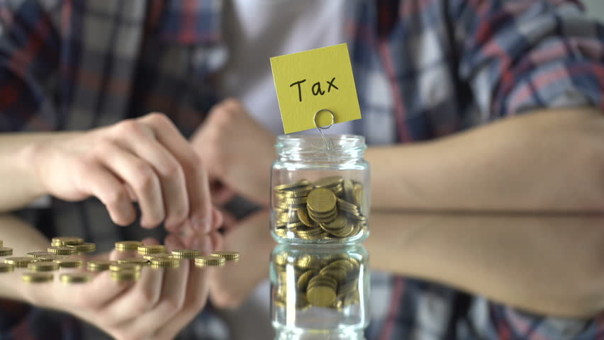 Tax word written above glass jar with money, official extortion concept, economy