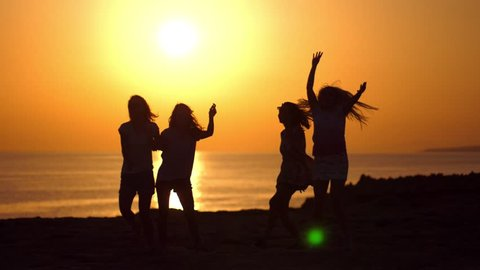 Dancing girls silhouettes at beach sunset. Playful girls enjoying beach party in gloaming. Bachelorette party at seacoast. Tomorrow married. Women silhouettes in evening sunset. Cyprus beach party