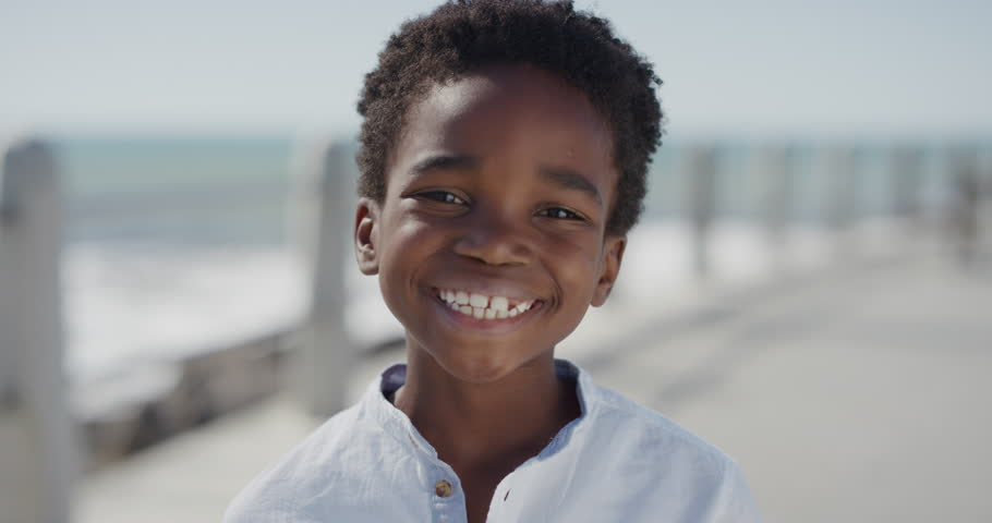 Close up portrait happy african american boy smiling cheerful enjoying warm summer vacation on seaside beach waterfront slow motion | Shutterstock HD Video #1013096855