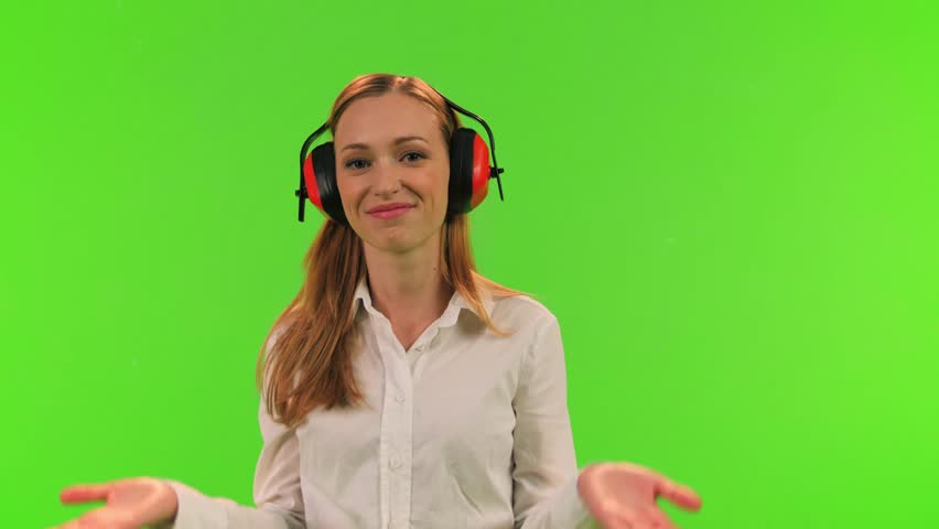 A disturb woman puts an earmuffs to protect her ears from noise, relaxes and smiles, over a green screen.
