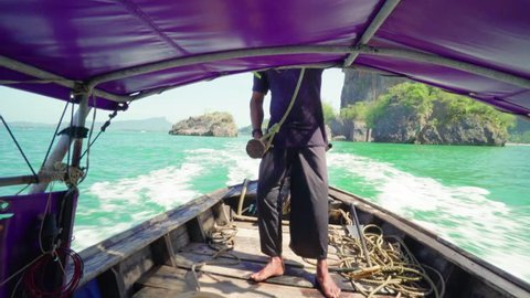 Unrecognizable man drives a long-tail thai boat with outboard motor 4K