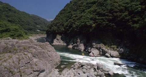 Aerial approach shot as raft capsizes in the whitewater on the Yoshino River in Tokushima Japan 60fps for slow motion