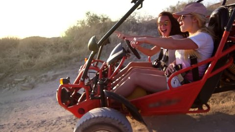 Young girls go on dune buggy on dirt road enjoying extreme rest. Riding along sandy road on beach buggy. Girls driving dune buggy. Extreme trip on earth road. Extreme vacation ride