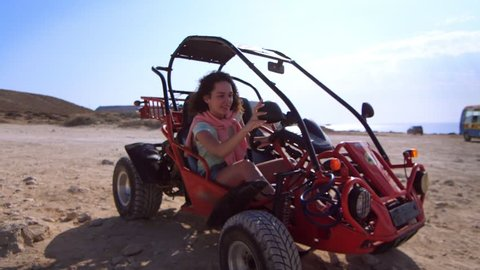 Brunette woman looking mirror in sand buggy car. Happy woman enjoy desert buggy drive at summer vacation time. Extreme entertainment in desert. Female tourist preparing to ride on buggy car