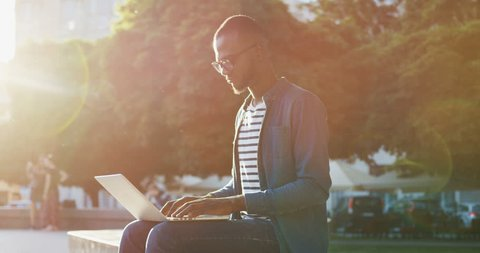 Silhouette of the young African American man in glasses sitting on the banch in the city center and typing on the laptop computer. Indoors.