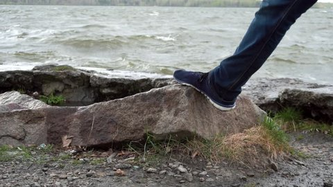 Close up of leg of a man wearing jeans standing on a rock in the river. Sneakers stepping on a stone. Close up of foot by the water on a stormy day