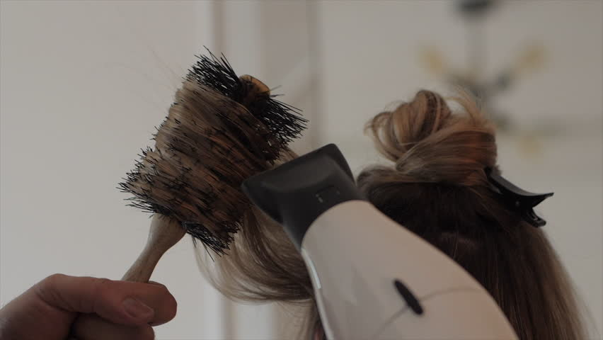 Hairdresser blowdrying and styling a blonde woman's long hair with a brush and hair dryer. Medium shot. 4K UHD 16:9