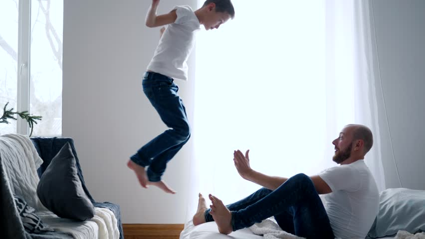 Happy family idyll, son jumps in hands father and they fall on a bed in slow motion | Shutterstock HD Video #1013180975