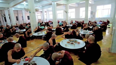 BAGO, MYANMAR - FEBRUARY 15, 2018: The dining room of Kha Khat Waing Kyaung Monastery during the lunch of bhikkhu monks, on February 15 in Bago.