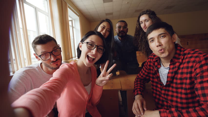 Point of view shot of attractive young men and women taking selfie in lecture hall, posing with textbook and showing hand gestures and expressive faces. | Shutterstock HD Video #1013200445