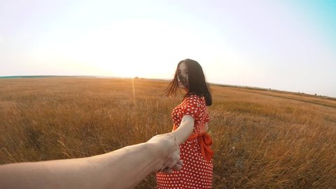 follow me. pretty portrait brunette girl goes with a man by the hand on nature field romance love. slow motion video. girl lifestyle and man walking call beckoning finger. follow me concept