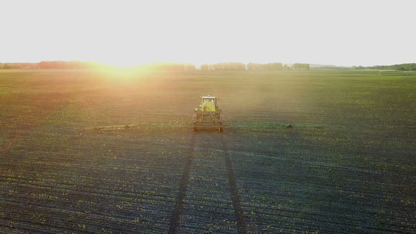 Shooting from a drone sprayer in a field at sunset. Top view of the operating tractor sprayer in the field on the farm.   Shutterstock HD Video #1013209115