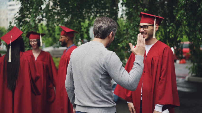 College professor is congratulating his student after graduation ceremony hugging him and shaking hand, teacher is proud of young man and wishes him good luck.