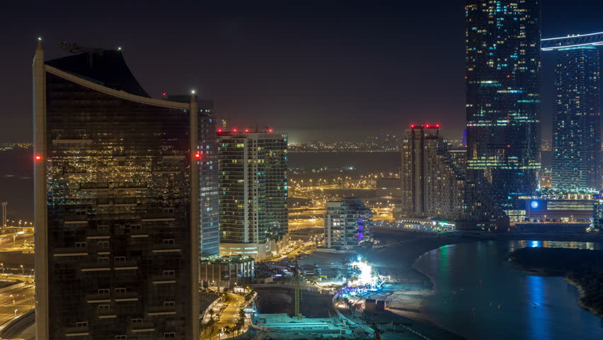 Skyscrapers on Al Reem Island in Abu Dhabi night timelapse from above. Aerial citiscape from Al Reem Island with illuminated buildings. Traffic on the road