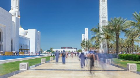 Sheikh Zayed Grand Mosque timelapse in Abu Dhabi, the capital city of United Arab Emirates. People walking on alley. Blue sky at sunny day
