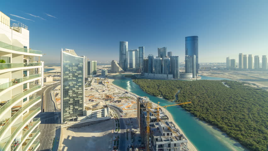 Buildings on Al Reem island in Abu Dhabi timelapse from above. Aerial citiscape of Al Reem Island at evening, showing the reflection of buildings in the water and long shadows.