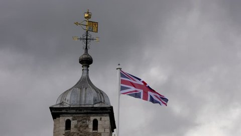 This a close up shot of one of the corner towers of the Tower of London. The shot shows the flag, weathercock and cloudsing due to high wind. The Crown Jewels are kept in the Tower of London.