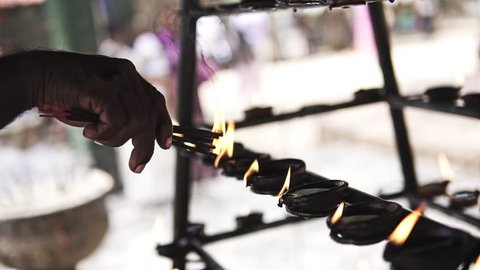 Close up follow focus video of burning oil lamps and incense joss sticks at temple. Traditional offering in buddhist and hindu temples