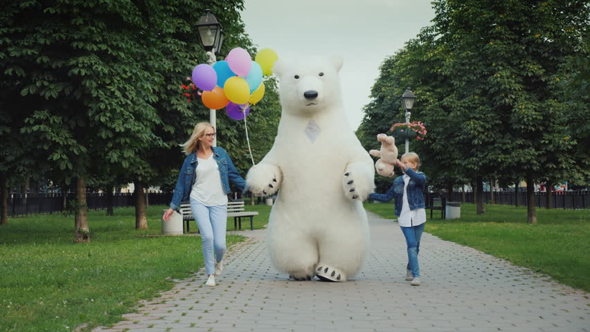 Mom and daughter and a polar bear are having fun along the street. Children's holiday concept