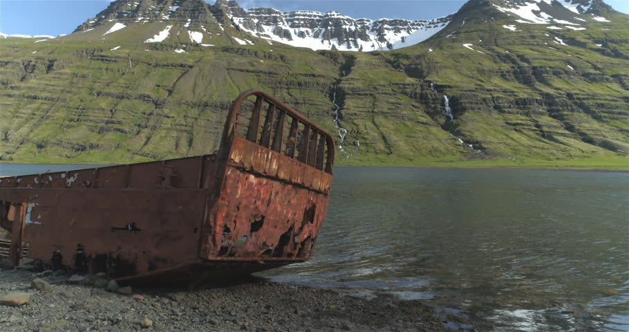 Aerial cinematic dolly shot of rusted shipwreck in mountain fjord, Mjoifjordur Iceland.