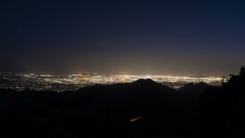 Time lapse of city lights at night with mountains and stars