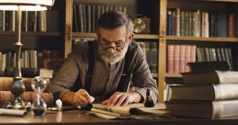 Portrait of the old man with gray beard and in glasses writing a letter with ink on the old wooden table in ancient style in the library cabinet.
