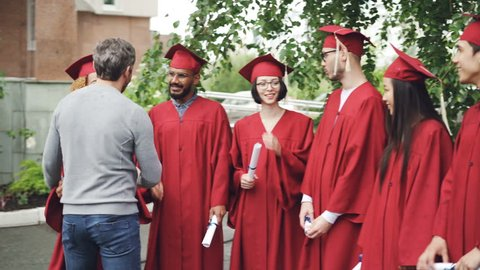 Bearded man proud teacher is congratulating graduates shaking hands and hugging them outdoors in college campus while students are talking and holding diplomas.