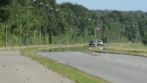 Cars approach on a road that seems to be wet so that thye mirror themseles, the road is dry and the effect is caused by a hot air layyer just aove the road's surface where heat distortion is also seen