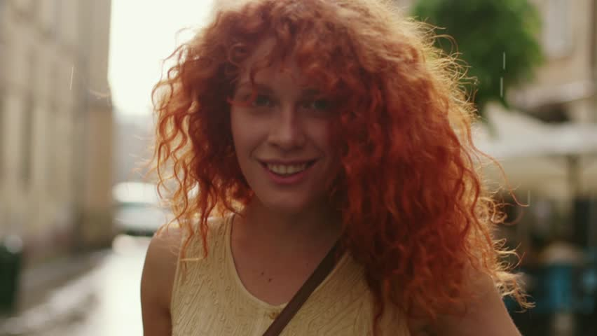 Woman with red curly hair walking in the rain on the street look at camera spinning happy smile cute beautiful portrait fashion water silhouette summer face female lonely stop close up | Shutterstock HD Video #1013312195