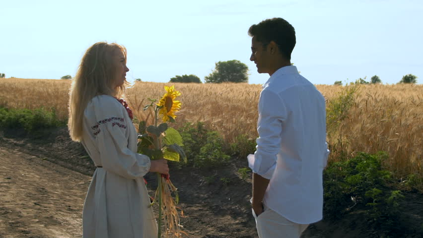 Slow Motion, Indian Man in Glasses and White Shirt Communicate with the Beautiful Woman in National Clothing and the Bunch of Wheat Sprouts and Sunflower in the Hands | Shutterstock HD Video #1013318525