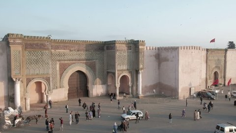Meknes, Morocco - April 4, 2018: High angle camera still view of angled Bab Mansour Gate and street traffic below