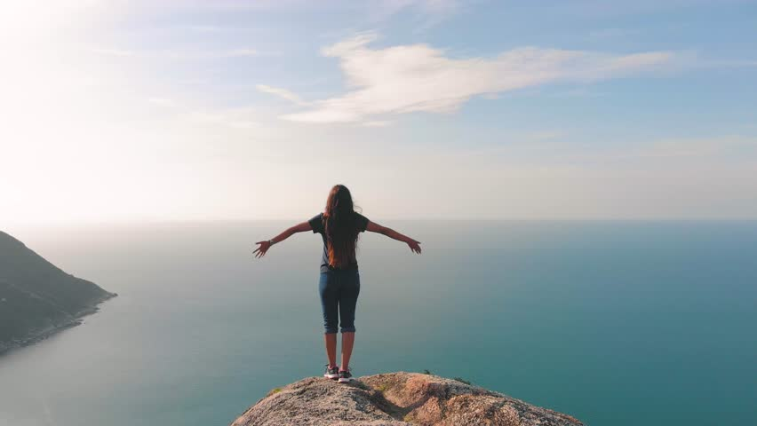 Woman traveller with arms raised on top of mountain looking at view Hiker girl lifting arm up celebrating scenic landscape enjoying vacation travel adventure nature Thailand asian girl | Shutterstock HD Video #1013339495