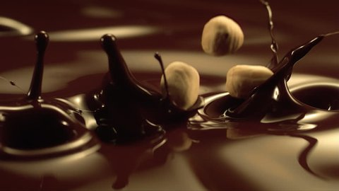 Falling hazelnuts in liquid chocolate in slow motion