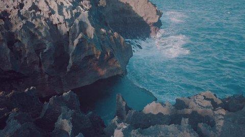 Angel's Billabong beach, the natural pool on the island Nusa Penida with waves crashing rocks, Indonesia
